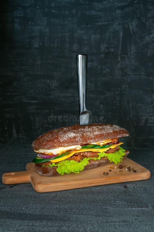 Сэндвич багета рож с салатом, красным луком, зажаренным куском свинины, огурцом и яичницами Сэндвич на деревянной прокалыванной д стоковое фото