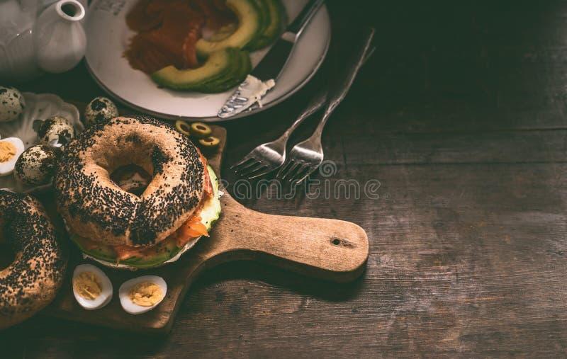 Сэндвич бейгл на разделочной доске Предпосылка деревянного стола завтрака с ингредиентами стоковое фото rf