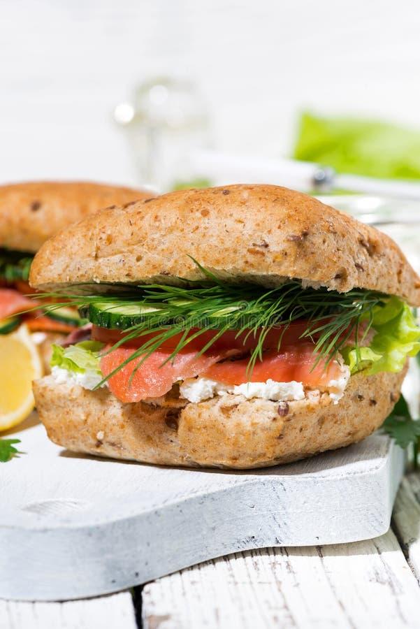 Сэндвич с посоленными рыбами и плавленым сыром на белой деревянной доске, вертикальном крупном плане стоковое фото rf