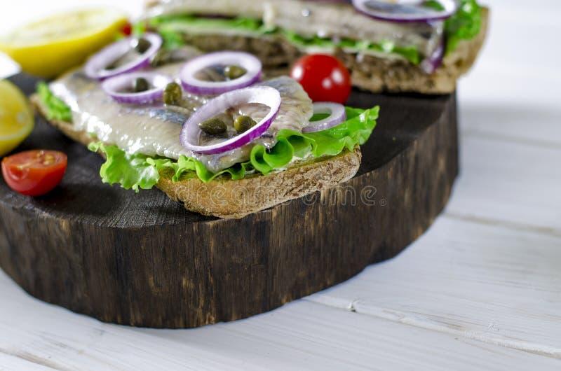 Сэндвич с посоленными сельдями, маслом и красным луком на старой деревенской разделочной доске r стоковые фото