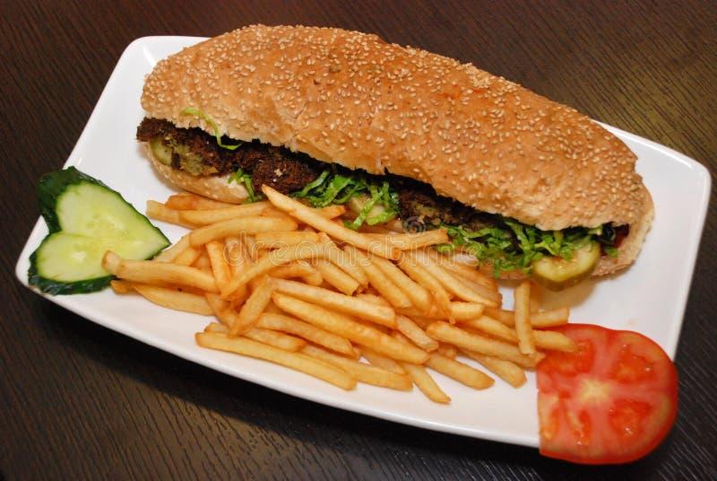 Сэндвич Falafel с французскими картофелем фри и овощами на белой плите стоковая фотография