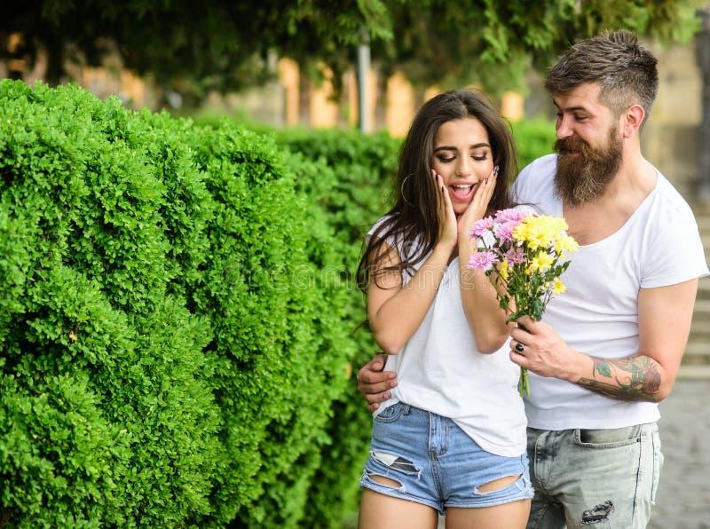 Сюрприз для ее Человек дает девушке букета цветка романтичную дату Предпосылка парка даты встречи пар Гай подготовило стоковые фото