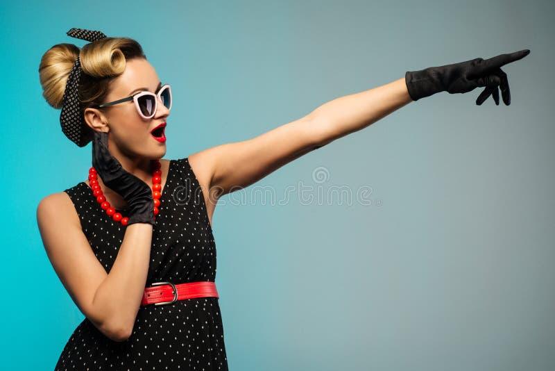 Сюрприз женщины показывая продукт Красивая девушка с вьющиеся волосы указывая к стороне представляющ продукт ваш стоковые фото