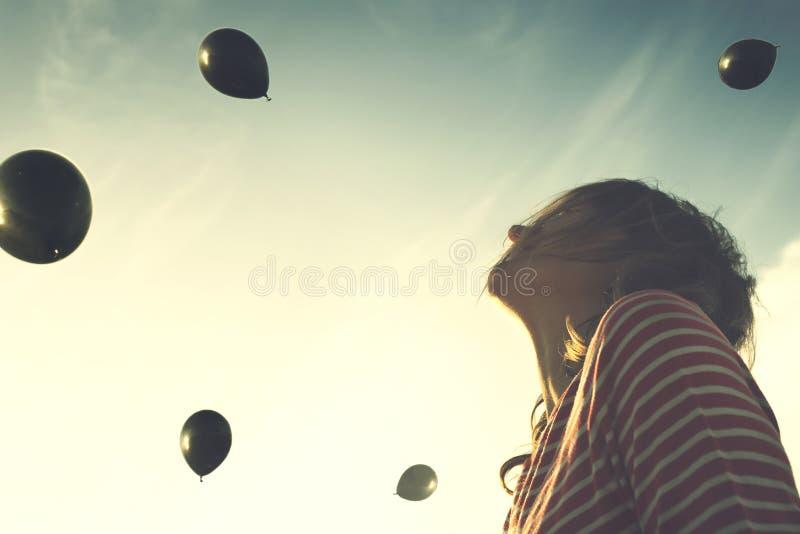 Сюрреалистический момент, женщина смотря удивленный с дождем черных шариков падая от неба стоковое изображение