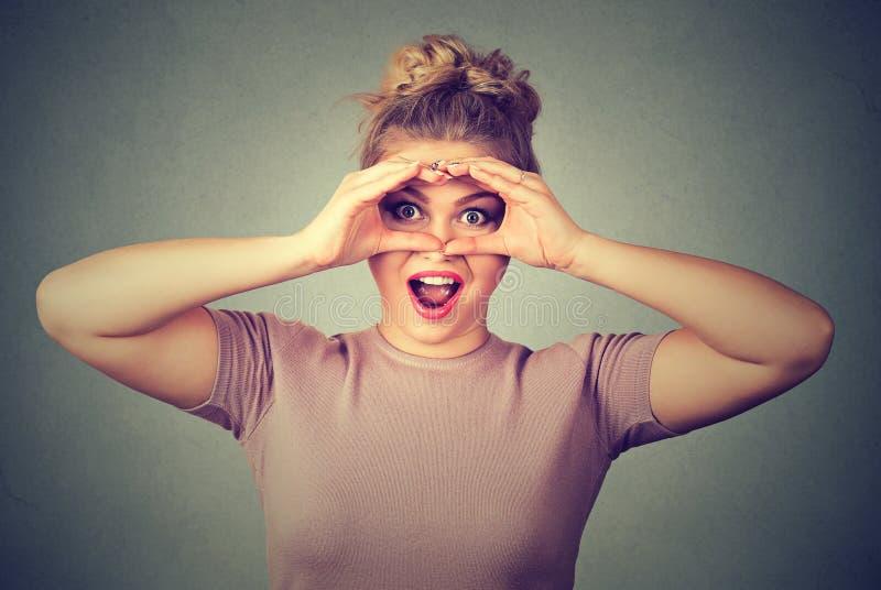 сярприз Stunned любознательная женщина peeking смотреть через пальцы любит бинокли стоковая фотография rf