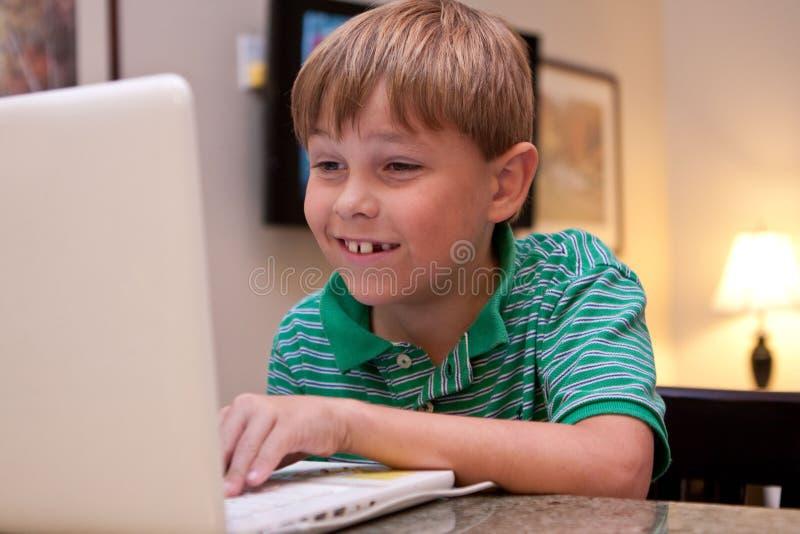 Ся мальчик используя белую компьтер-книжку стоковые фотографии rf
