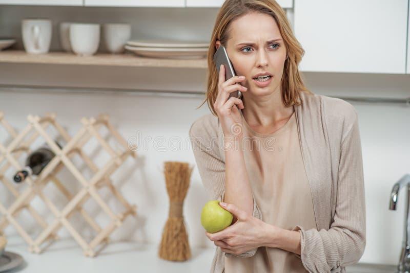 Слабонервная дама говоря на телефоне в комнате кашевара стоковое изображение rf