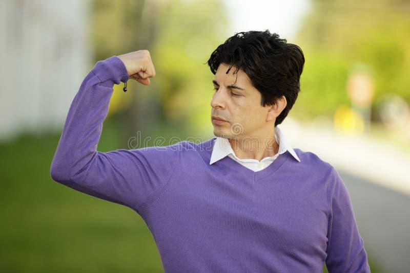 Слабый человек изгибая его мышцы стоковое изображение rf