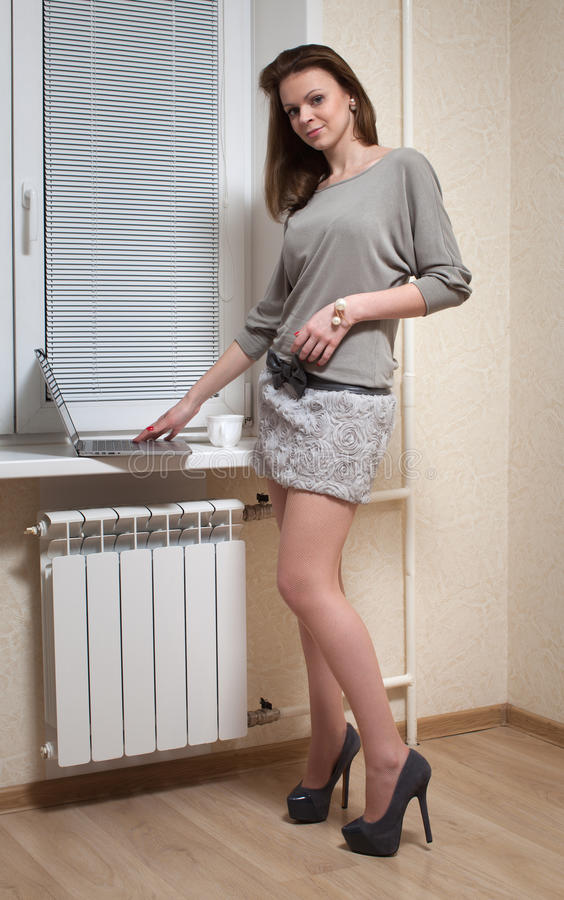 Славная блондинка на окне с компьтер-книжкой стоковая фотография