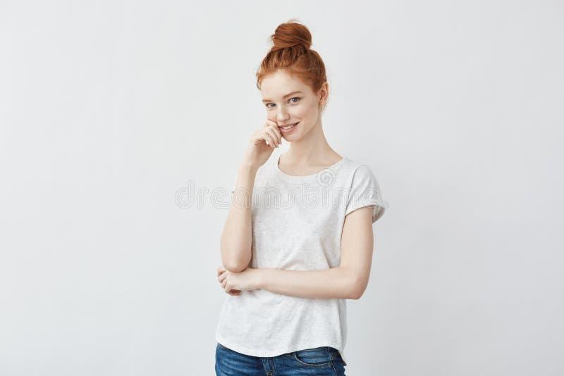 Славная девушка имбиря с ультрамодной плюшкой, усмехаясь смотреть прямо стоковое фото rf