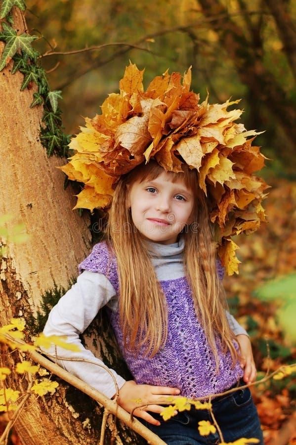 Славная девушка стоит в склонности парка осени против дерева На голове сплетенного венка листьев осени стоковое изображение rf