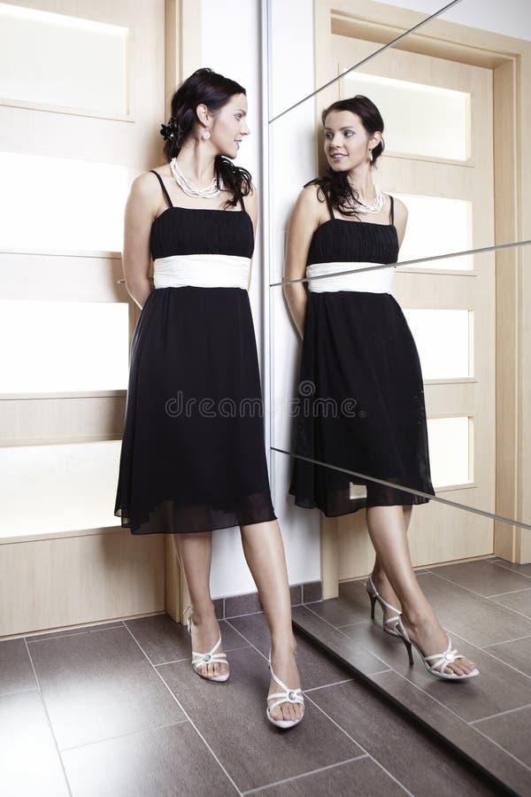 Славная женщина представляя в черном платье за mirrow стоковая фотография