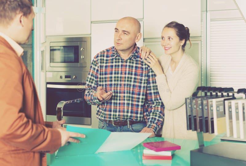 Славные клиенты продавца и супругов на мебели кухни стоковое изображение rf