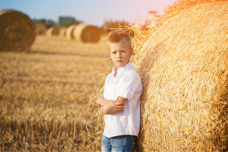 Славный мальчик в поле близко стога соломы на заходе солнца стоковое изображение rf