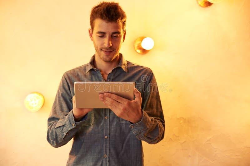 Славный молодой человек отправляя СМС на таблетке стоковые фотографии rf