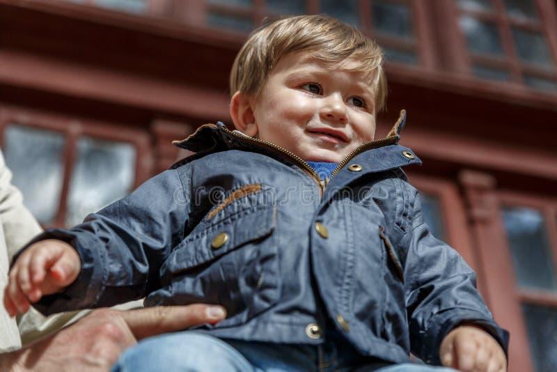 Славный ребенок смотрит вперед пока держал взрослым стоковое изображение