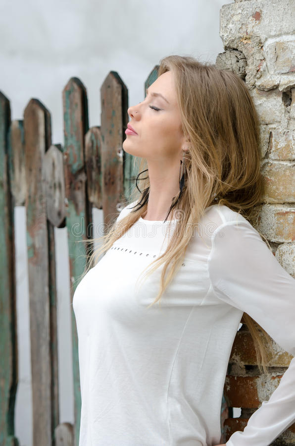 Сладостная белокурая склонность женщины против кирпичной стены стоковая фотография rf