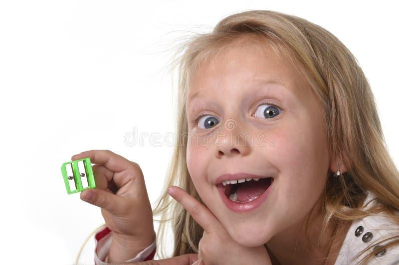 Сладостная красивая девочка при голубые глазы держа школьные принадлежности точилки для карандашей чертежа стоковые изображения