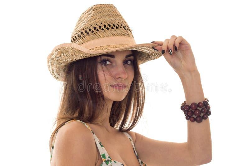 Сладостная молодая девушка брюнет в одеждах лета при цветочный узор и соломенная шляпа смотря изолированную камеру на белизне стоковое фото