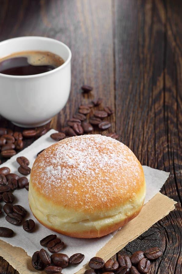 Сладостные донут и кофейная чашка на таблице стоковые фотографии rf