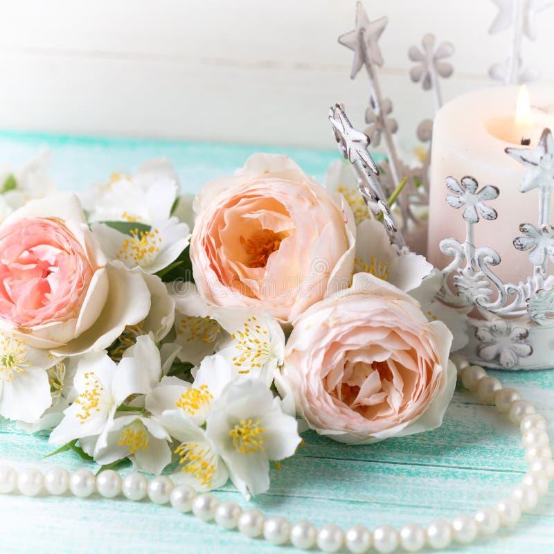 Сладостные пастельные розы, цветки жасмина и свеча стоковые изображения rf