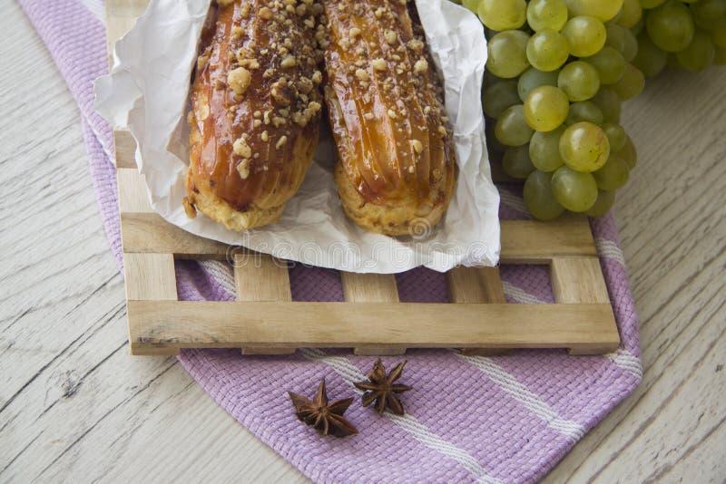 Сладостные eclairs и зеленые виноградины стоковые фото