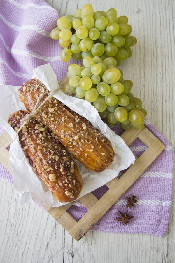 Сладостные eclairs и зеленые виноградины стоковые изображения rf