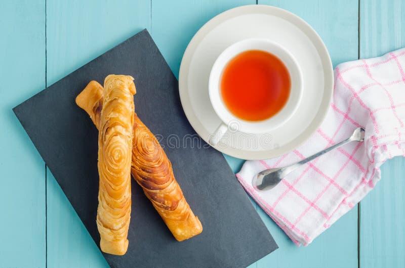Сладостный завтрак с печеньем и чаем слойки карри на голубом деревянном ба стоковые фотографии rf