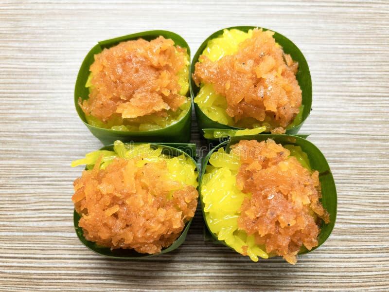 Сладостный липкий рис при заварной крем яичка и сладостное отбензинивание кокоса, обернутые в лист банана Популярный тайский десе стоковое фото rf