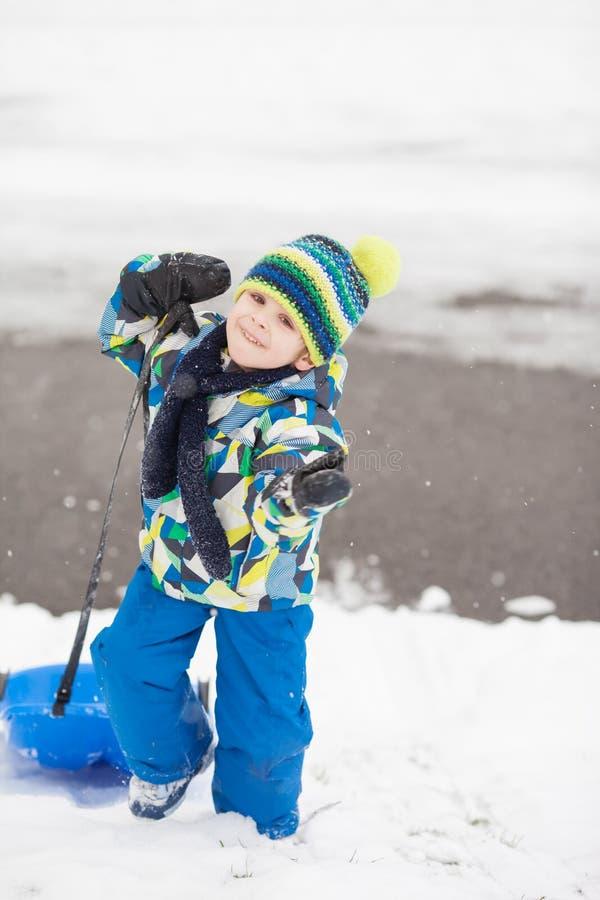 Сладостный мальчик, sledging в зимнем времени снега, имеющ потеху стоковое фото rf