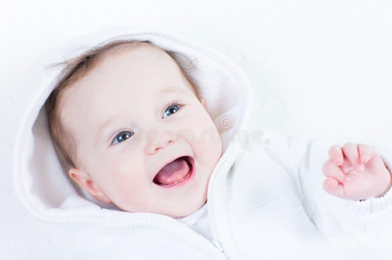 Сладостный младенец в белой куртке смеясь над и играя стоковое фото