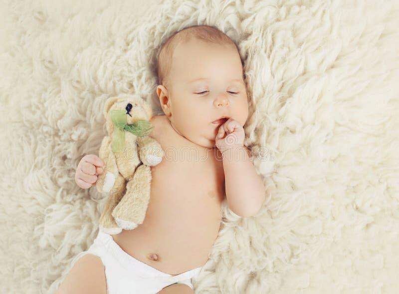 Сладостный младенец дома спать с плюшевым медвежонком стоковое фото