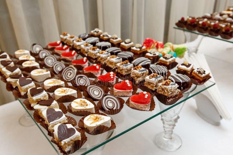 Сладостный шведский стол - шоколадные торты, суфле и швейцарские крены, поставляя еду стоковые изображения rf