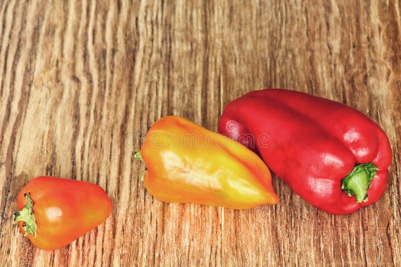 3 сладостных перца на коричневой деревянной предпосылке тонизированное изображение стоковая фотография rf