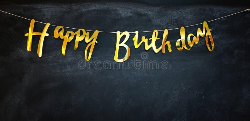 С днем рождения золотая гирлянда на темной стене стоковые изображения rf
