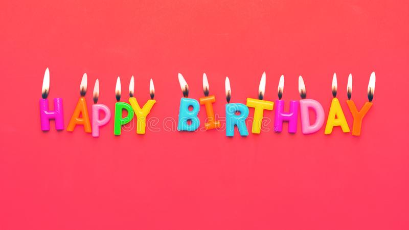 С днем рождения красочные свечи на розовой бумажной предпосылке стоковое фото rf