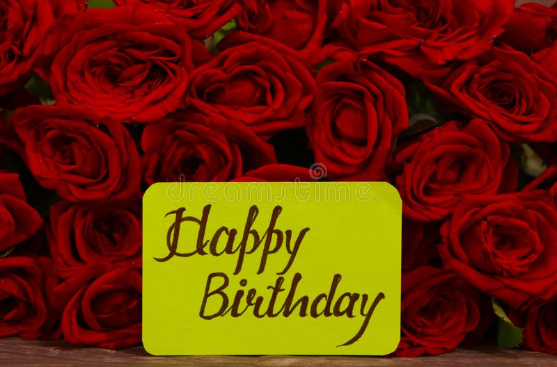 С днем рождения текст с красными розами в кучке как фон стоковое фото rf