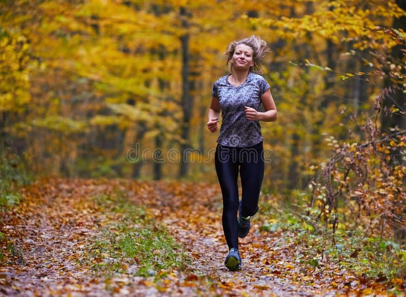 След молодой женщины бежать в лесе стоковое фото