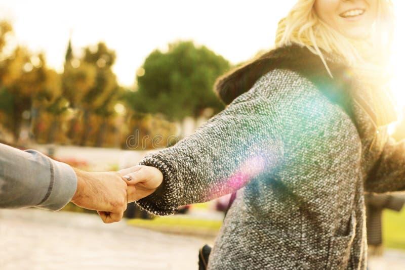 Следовать мной - девушка вытягивая руку человека стоковое изображение
