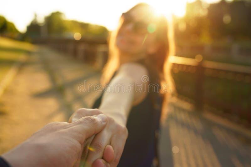 Следовать мной - счастливая молодая женщина вытягивая руку ` s парня - рука об руку стоковые изображения