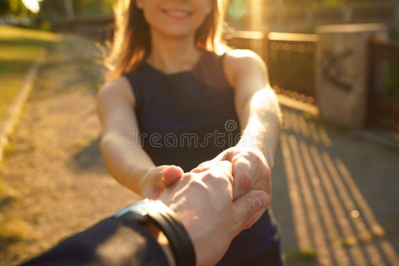 Следовать мной - счастливая молодая женщина вытягивая руку ` s парня - рука об руку стоковые изображения rf