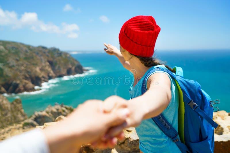 Следовать мной - счастливая молодая женщина в красной шляпе и с рюкзаком b стоковые фотографии rf