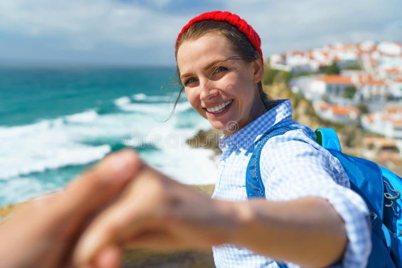 Следовать мной - счастливая молодая женщина в красной шляпе и с рюкзаком b стоковые изображения rf