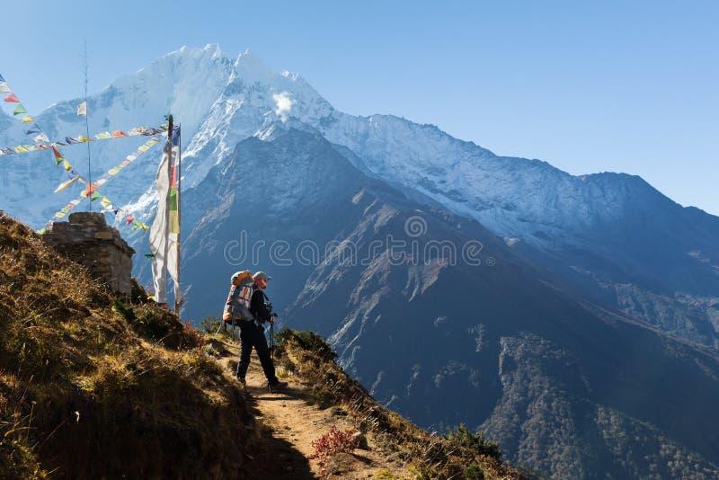 След положения backpacker женщины, pe снега гребня горы Kangtega стоковая фотография rf