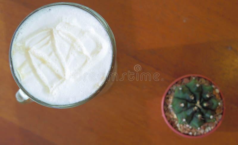 Сливк горячих кофе и кактуса на деревянном столе, селективном фокусе стоковая фотография