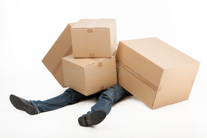 Слишком тяжелые коробки. Лежать работника доставляющего покупки на дом покрытый с стогом cardb стоковое фото