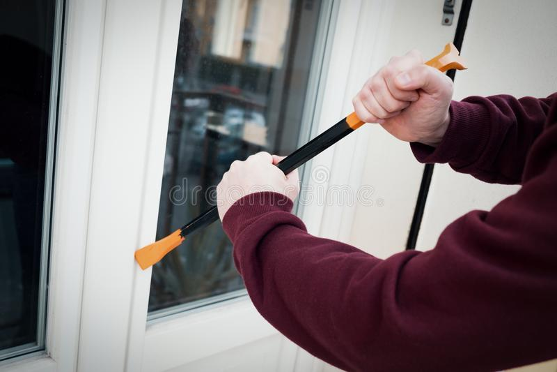 С капюшоном взломщик принуждая замок окна для того чтобы сделать похищение в доме стоковая фотография rf