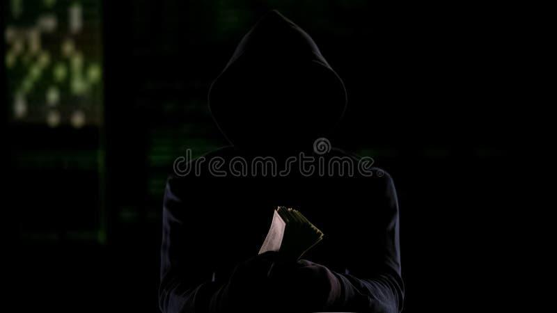С капюшоном человек в темноте держа наличные деньги, вознаграждение убийств-для-найма или украденные деньги стоковое фото rf