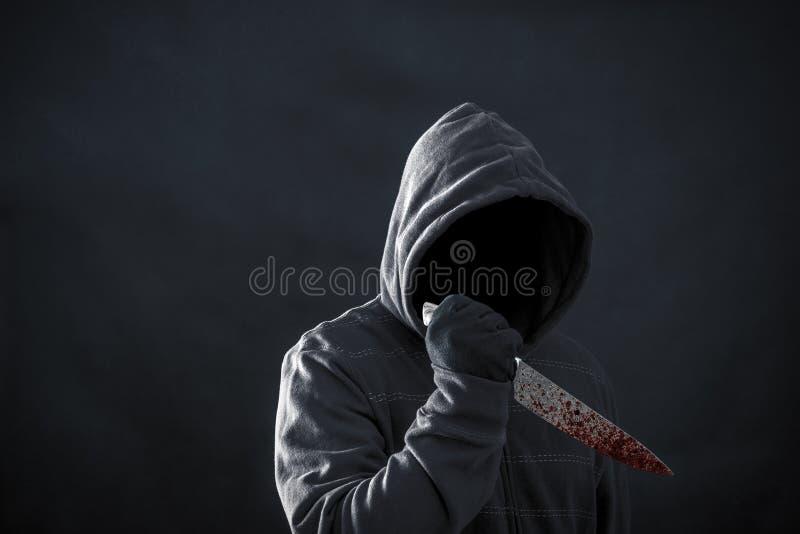 С капюшоном человек с кровопролитным ножом стоковые изображения rf