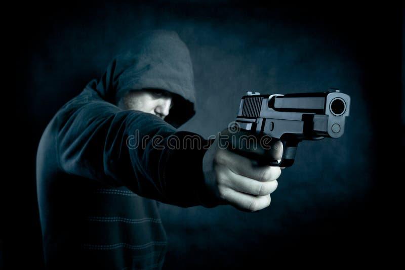 С капюшоном человек с оружием в темноте стоковое фото rf